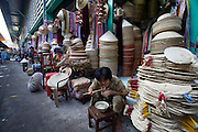 Cholon (Chinatown). Binh Tay Market. Woman selling traditional cone hats having Pho for breakfast.