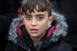 © Licensed to London News Pictures . 24/10/2016 . Calais , France . A Kurdish boy reportedly aged ten years old , leaving the Jungle migrant camp in Calais , Northern France , with their parents , on the day of a planned eviction and start of the destruction of the camp . Photo credit: Joel Goodman/LNP