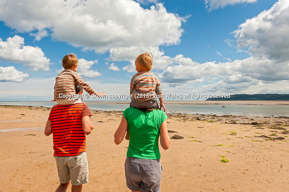 Family on beach at Red Wharf Bay<br /> Traeth Coch<br /> Anglesey<br /> North<br /> Coastal Scenery