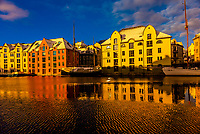 Beautiful former warehouses along the canal in the Brosundet quarter in Art Nouveau (Jugendstil) architectural style, Alesund, Norway. Most of the town was rebuilt after a fire in 1904, with the help of Kaiser Wilhelm of Germany, who often vacationed in the area.