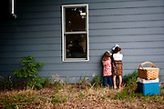 Tinsley Sears, left, and Brecklyn Bronyx count to ten before turning and searching for their friends and family during a game of hide and go seek July 28, 2013 after a church service and dinner in Brownlee, Neb. Photo by Lauren Justice