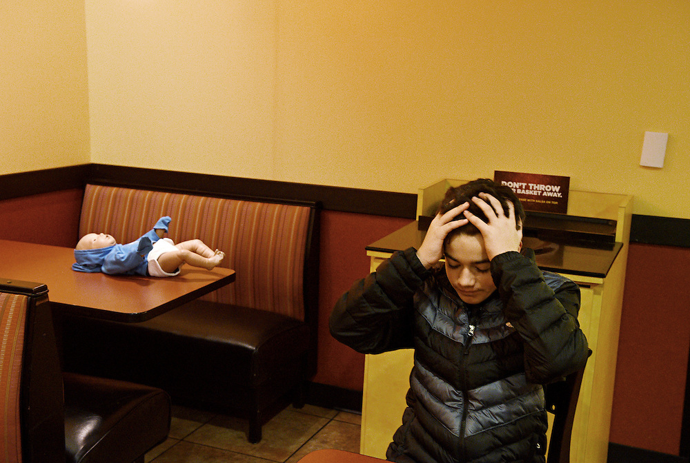 "Patrick Mason, 14, of Lebanon reacts as his interactive baby doll begins to cry as he settles in to eat dinner at Moe's in West Lebanon, Jan. 15, 2015. The dolls are given to Lebanon Middle School health class students over night for lessons on parenting. ""This is so awful. I could not imagine six months of this,"" said Mason."