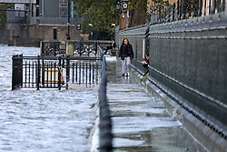 © Licensed to London News Pictures. 04/11/2013. A very high tide on Monday afternoon saw the river Thames breach the river wall in places and flood footpaths. The river is pictured here at the Old Royal College where high tide was at 1.45pm and pedestrians got their feet sodden and had to cling on to the railings to avoid the water. Credit : Rob Powell/LNP