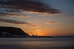 © Licensed to London News Pictures. 28/05/2015. Scarborough, UK. The early morning sun rises over the South bay in Scarborough, temperatures in the UK are set to return to average for this time of year by the weekend. Photo credit : Andrew McCaren/LNP