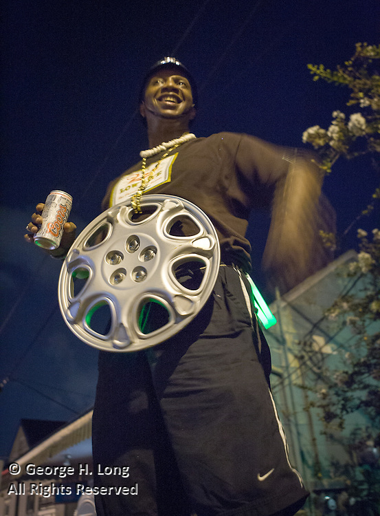 Leroy Mitchell watches from above the Mid-Summer Mardi Gras Celebration; While many New Orleanians had already evacuated for Hurricane Katrina, others celebrated Mid-Summer Mardi Gras  with the Krewe of Oak outside the Maple Leaf Bar on Oak Street.  August 27, 2005