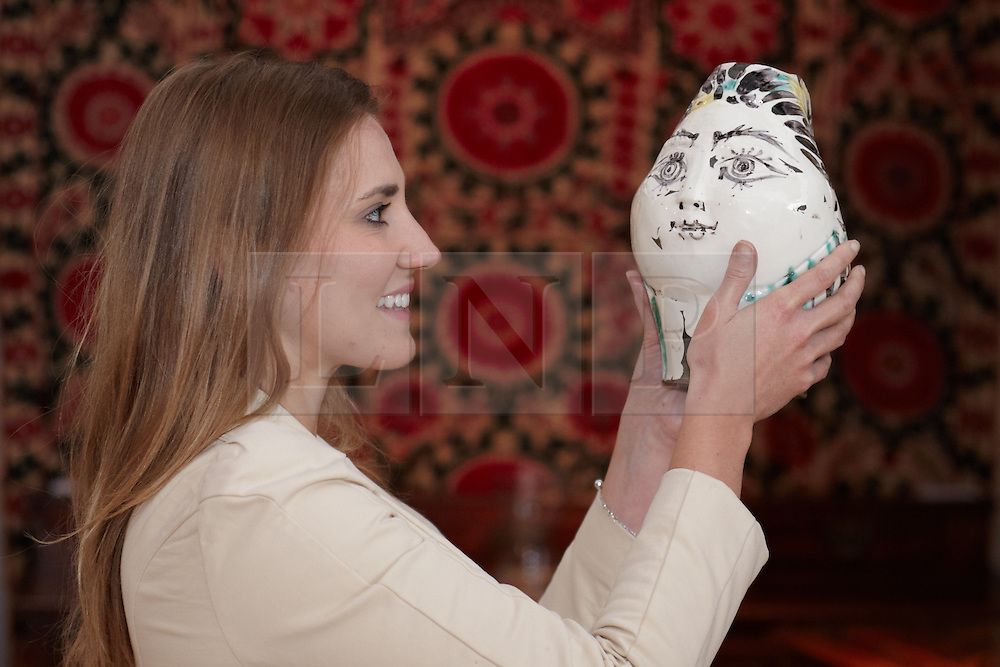 © licensed to London News Pictures. LONDON, UK  08/06/2011. Elvira Pilatti examines a vase, valued at  £20,000, made by Picasso at the Olympia International Fine Art & Antiques Fair. In total 30,000 items are on sale from 150 dealers and each is vetted for authenticity by a panel of experts. The show opens in Olympia tomorrow (Thursday) and runs for 11 days. Please see special instructions for usage rates. Photo credit should read CLIFF HIDE/LNP