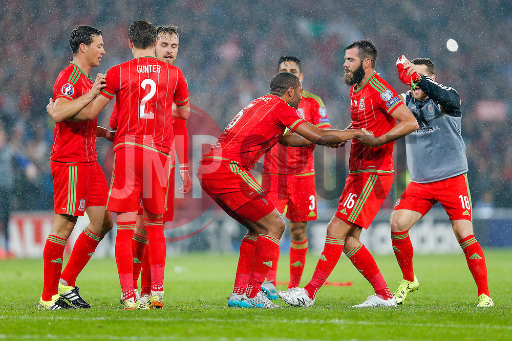 Joe Ledley (Crystal Palace) hels up Ashley Williams (Capt) (Swansea City) as the players celebrate after Wales win the match 1-0 to top their UEFA2016 Qualifying Group - Photo mandatory by-line: Rogan Thomson/JMP - 07966 386802 - 12/06/2015 - SPORT - FOOTBALL - Cardiff, Wales - Cardiff City Stadium - Wales v Belgium - EURO 2016 Qualifier.
