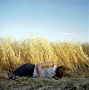 Young woman lying in oat field with face obstructed by hair