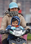 Woman rides motorcycle with a baby in Bac Ninh Province in Vietnam on Jan 10, 2013..(Photo by Kuni Takahashi)
