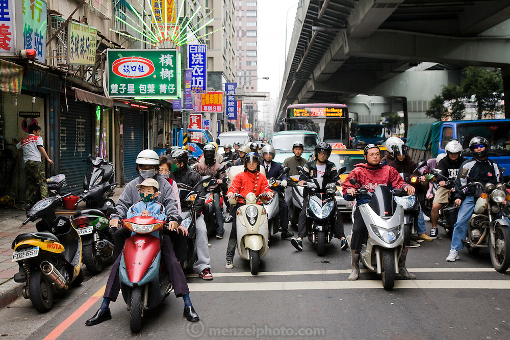Motorcycle traffic yields to pedestrians on a busy street in Taipei, the capital of Taiwan.
