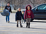 """17 MARCH 2020 - DES MOINES, IOWA: A family walks to a food distribution in the parking lot of Carver Elementary School in Des Moines. Des Moines Public Schools are closed for at least 30 days because of the Coronavirus outbreak. Des Moines area religious organizations and food banks are working together to bring free food to children in at risk communities. Volunteers and workers are practicing """"social distancing"""" by leaving the food packages on the pavement and recipients pick up the packages. Tuesday, the Governor of Iowa ordered all restaurants and bars to close or go to take out only. The Iowa Department of Public Health has urged all public buildings, like libraries and schools, to close, and all schools in Iowa are closed for at least 30 days.     PHOTO BY JACK KURTZ"""