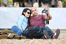© Licensed to London News Pictures. 23/05/2015. Brighton, UK. A couple taking a selfie on Brighton beach, today May Bank Holiday Weekend, today May 23rd 2015. Photo credit : Hugo Michiels/LNP