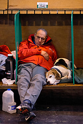 © London News Pictures. 07/03/2013. Birmingham, UK. An owner sleeping with his Beagle on Day one of Crufts at the Birmingham NEC Arena on March, 07, 2013 in Birmingham, England.  Crufts, which is the largest annual dog show in the world, hosts over 20,000 dogs and owners who compete in a variety of categories. Photo credit : Ben Cawthra/LNP