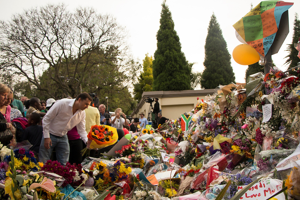 Hundreds of people converged to Mandela's house in Johannesburg to pay their respect and drop off flowers and memorials, on Saturday Dec.7 2013.