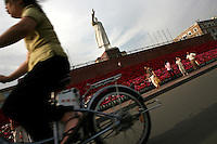 A woman rides her bike in front of a statue of Chairman Mao in Kunming, the capital of Yunnan province in China. (Photo/Scott Dalton)