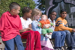 Group of young friends out in the park together; one of them holding a baby,