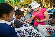 "30 JANUARY 2013 - PHNOM PENH, CAMBODIA:   A Cambodian woman buys black ribbons to wear to mark her mourning for late King Norodom Sihanouk. Sihanouk (31 October 1922 - 15 October 2012) was the King of Cambodia from 1941 to 1955 and again from 1993 to 2004. He was the effective ruler of Cambodia from 1953 to 1970. After his second abdication in 2004, he was given the honorific of ""The King-Father of Cambodia."" Sihanouk held so many positions since 1941 that the Guinness Book of World Records identifies him as the politician who has served the world's greatest variety of political offices. These included two terms as king, two as sovereign prince, one as president, two as prime minister, as well as numerous positions as leader of various governments-in-exile. He served as puppet head of state for the Khmer Rouge government in 1975-1976. Most of these positions were only honorific, including the last position as constitutional king of Cambodia. Sihanouk's actual period of effective rule over Cambodia was from 9 November 1953, when Cambodia gained its independence from France, until 18 March 1970, when General Lon Nol and the National Assembly deposed him. Upon his final abdication, the Cambodian throne council appointed Norodom Sihamoni, one of Sihanouk's sons, as the new king. Sihanouk died in Beijing, China, where he was receiving medical care, on Oct. 15, 2012. His cremation is scheduled to take place on Feb. 4, 2013. Over a million people are expected to attend the service.        PHOTO BY JACK KURTZ"