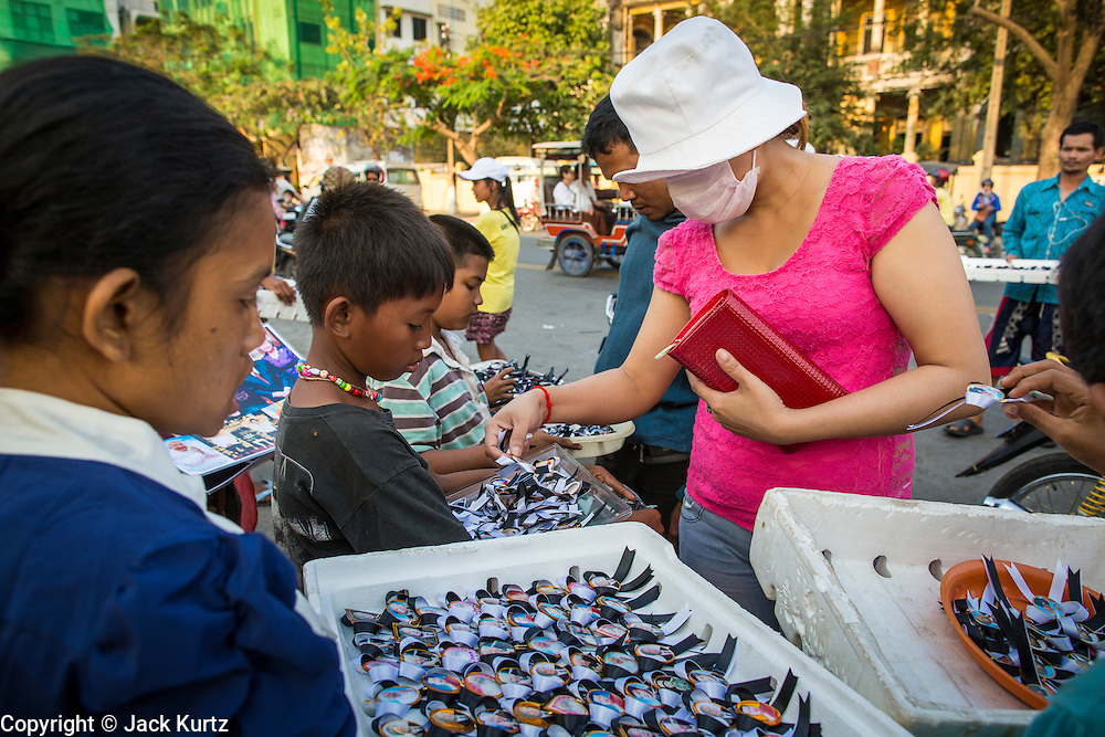 """30 JANUARY 2013 - PHNOM PENH, CAMBODIA:   A Cambodian woman buys black ribbons to wear to mark her mourning for late King Norodom Sihanouk. Sihanouk (31 October 1922- 15 October 2012) was the King of Cambodia from 1941 to 1955 and again from 1993 to 2004. He was the effective ruler of Cambodia from 1953 to 1970. After his second abdication in 2004, he was given the honorific of """"The King-Father of Cambodia."""" Sihanouk held so many positions since 1941 that the Guinness Book of World Records identifies him as the politician who has served the world's greatest variety of political offices. These included two terms as king, two as sovereign prince, one as president, two as prime minister, as well as numerous positions as leader of various governments-in-exile. He served as puppet head of state for the Khmer Rouge government in 1975-1976. Most of these positions were only honorific, including the last position as constitutional king of Cambodia. Sihanouk's actual period of effective rule over Cambodia was from 9 November 1953, when Cambodia gained its independence from France, until 18 March 1970, when General Lon Nol and the National Assembly deposed him. Upon his final abdication, the Cambodian throne council appointed Norodom Sihamoni, one of Sihanouk's sons, as the new king. Sihanouk died in Beijing, China, where he was receiving medical care, on Oct. 15, 2012. His cremation is scheduled to take place on Feb. 4, 2013. Over a million people are expected to attend the service.        PHOTO BY JACK KURTZ"""
