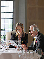 Business man and woman sitting at restaurant table reading documents