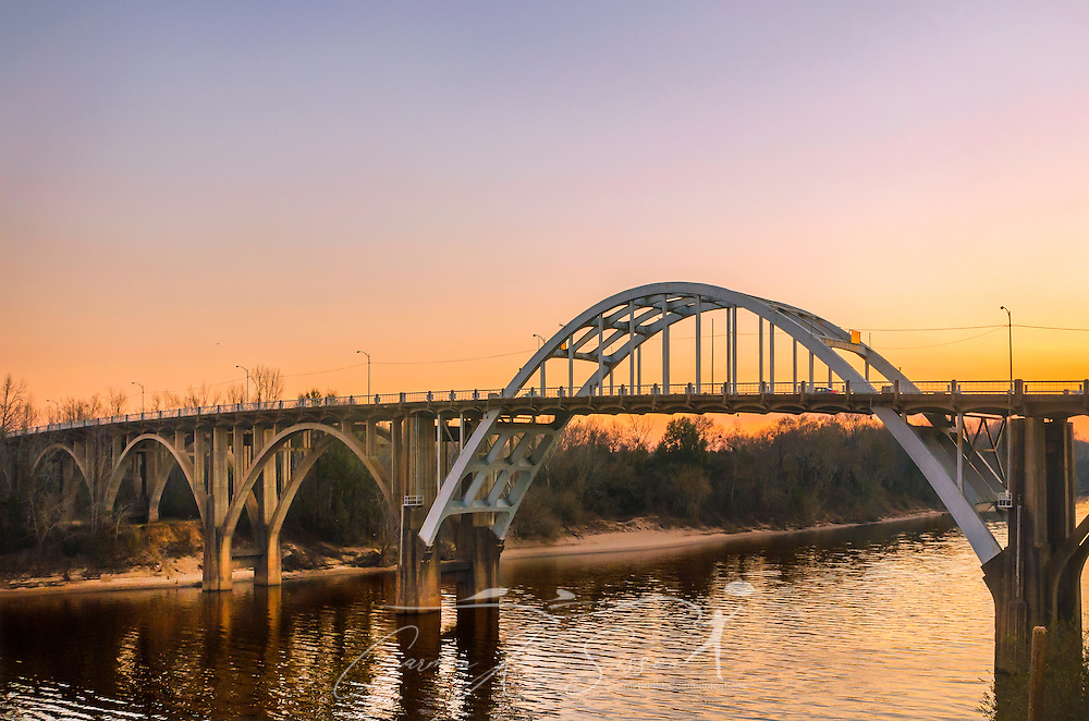 """The sun sets behind the Edmund Pettus Bridge, Feb. 14, 2015, in Selma, Alabama. The bridge was the site of """"Bloody Sunday,"""" where state troopers and local law enforcement attacked civil rights activists as they attempted to march from Selma to Montgomery, March 7, 1965. (Photo by Carmen K. Sisson/Cloudybright)"""