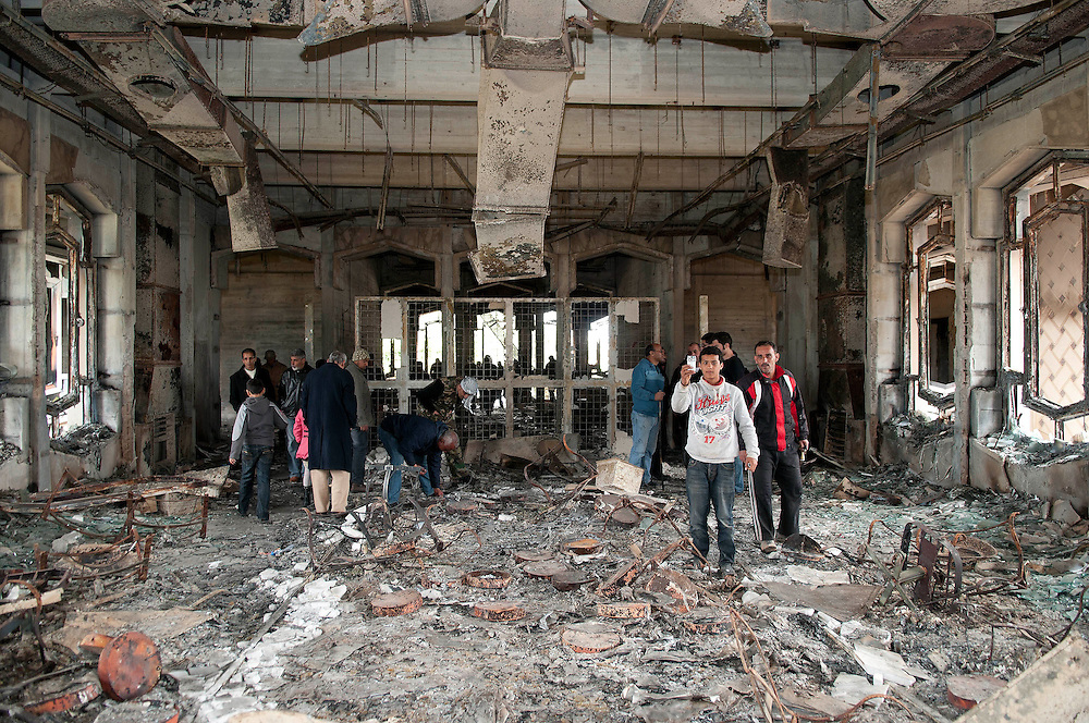 A boy uses his mobile phone to take a picture of a destroyed room in Muarmar Gaddafi's former palace in the Libyan city of Benghazi.