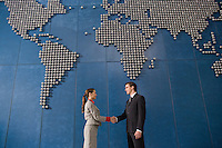Business colleagues shaking hands in front of world map on office wall