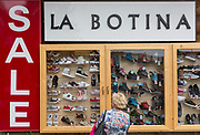 A local lady shopper looks at a display of a Polish shoe shop window, on 16th September 2019, in Zakopane, Malopolska, Poland.
