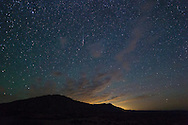 A Delta Aquarid meteor burns up in the sky above the Pryor Mountains. The glow in the distance is light pollution from Billings.