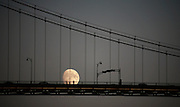 People stand on the Lions Gate Bridge as the moon rises behind in West Vancouver, BC. (2006)