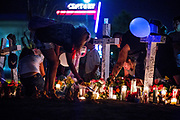 Thousands of people gathered at the improvised memorial across the street from the Century 16 Movie Theater after a vigil was held for the killed and wounded in the Aurora shooting. The assumed killed, James Holmes, is to appear in court Monday.