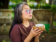 """17 MARCH 2018 - BANGKOK, THAILAND:  A woman prays before presenting cooked sticky rice to monks during a """"sticky rice merit making"""" in Lumpini Park in Bangkok. Sticky rice merit making is a merit making in the Isan / Lao style, when people present small amounts of cooked sticky rice (also known as glutinous rice) to Buddhist monks. Isan is the northeast region of Thailand.   PHOTO BY JACK KURTZ"""