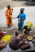 PUTTARPATHI, INDIA - 27th October 2019 - Women buying flowers at a market in Puttarpathi, Andhra Pradesh, South India