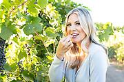 Woman tasting a Syrah grapes at Holeinsky Vineyard and Winery in Buhl, Idaho.