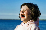 Young girl laughing hysterically, Cape Cod