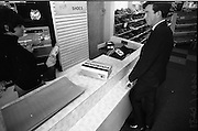 """24/05/1966<br /> 05/24/1966<br /> 24 May 1966<br /> Farren's shoe Store, Parnell Street, Dublin. View of the shop counter and till note the """"old money"""" in the cashier's hand."""