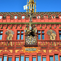 Rathaus Town Hall Fa&ccedil;ade Detail in Basel, Switzerland <br /> Beneath the gilded spire called a fl&egrave;che on the Rathaus is a statue of a Swiss Pikeman.  They were mercenary soldiers during the Middle Ages and Renaissance.  In the battlements are the coat of arms from the 12 cantons that constituted the Swiss Confederation in 1504 when this stunning town hall was built in Basel, Switzerland.