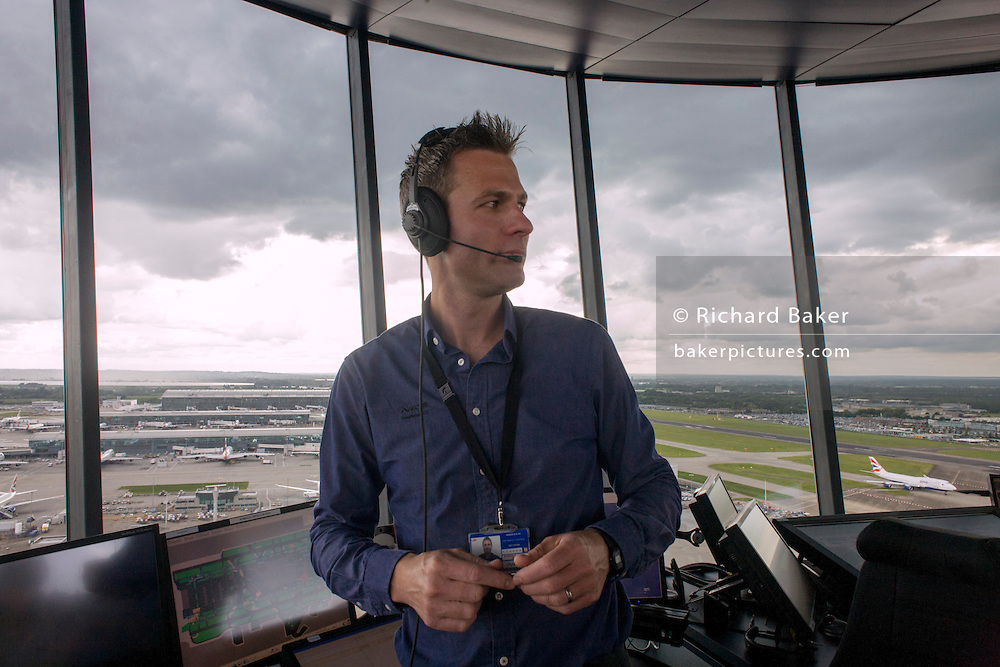 NATS Heathrow air traffic controller in control tower at Heathrow airport, London.