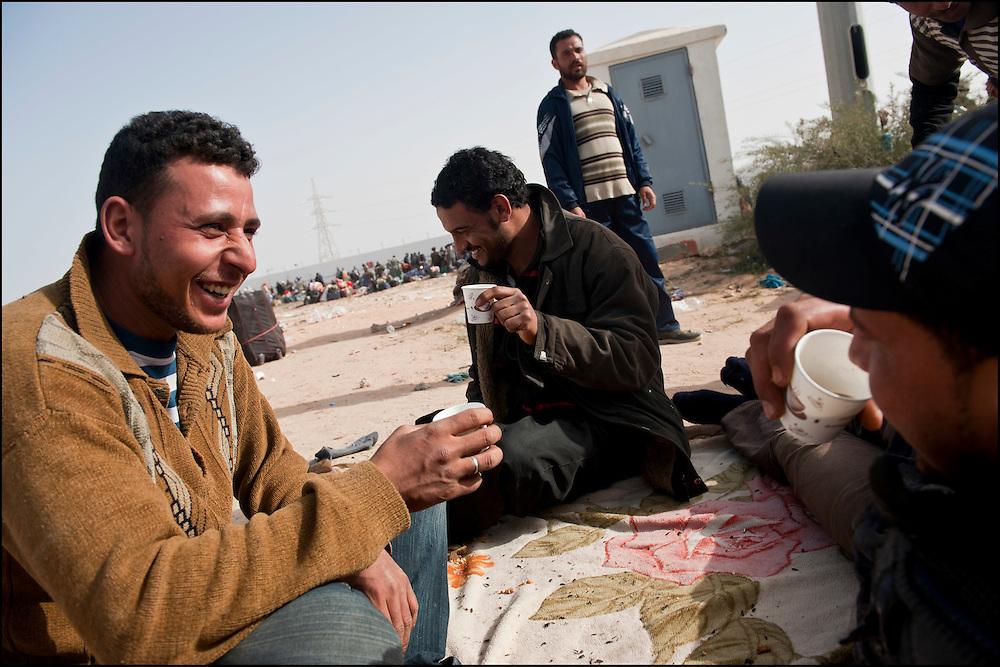 Des réfugiés Egyptiens boivent un café en attendant leur départ en bus vers le camp humanitaire Choucha situé à quelques kilomètres du poste frontière Ras Jedir. Plus de 140 000 réfugiés ont déjà quitté la Libye par la Tunisie ou l'Egypte et des milliers continuent d'arriver chaque jours. Vendredi 4 Mars 2011, Ras Jedir, Tunisie..© Benjamin Girette/IP3 press