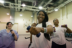 Althea works on her upper body strength by punching the air with small weights.
