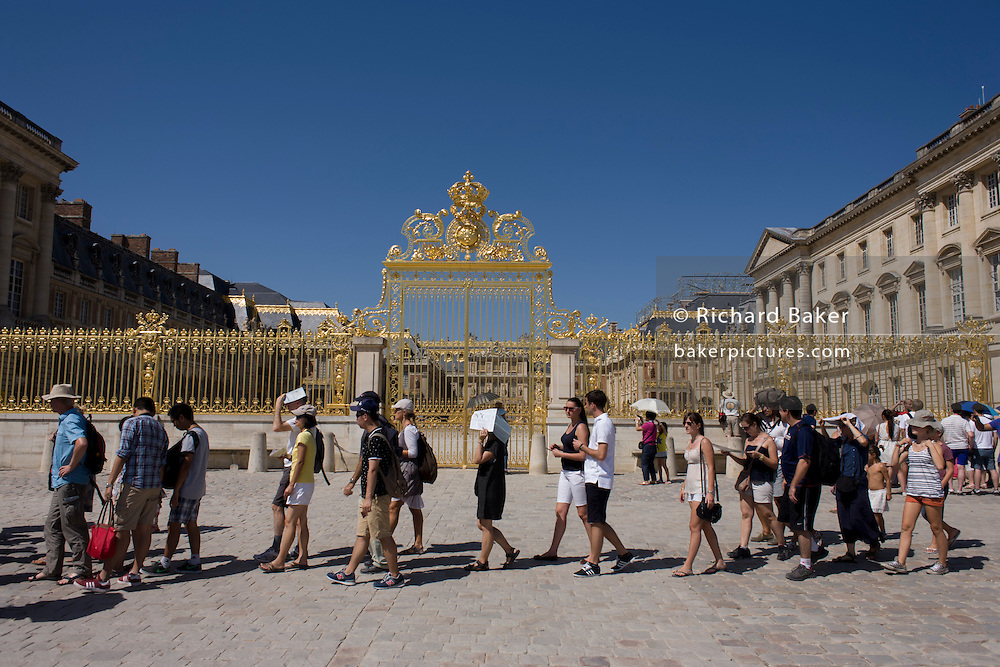 Tourists queue to gain entrance below the golden gates of  the Palace of Versaille, near Paris. A total of 100,000 gold leaves were crafted into the shapes of fleur de lys, crowns, masks of Apollo, cornucopias and the crossed capital Ls representing the Sun King. Private donors contributed £4 million to rebuild the 15-ton work, and a plethora of historians and top craftsmen - sculptors, gilders, wrought iron craftsmen and ornament makers - were drafted in to ensure an exact replica of the original built by Jules Hardouin-Mansart in the 1680s.