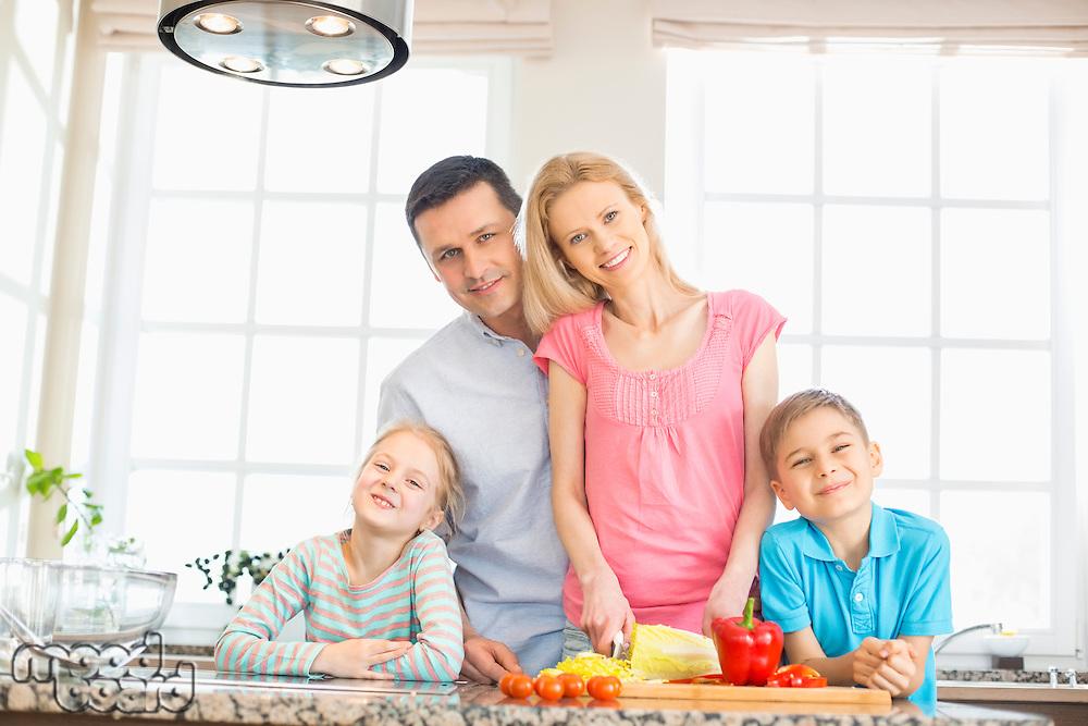 Portrait of happy family preparing food in kitchen