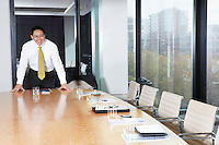 Business man standing behind table in boardroom