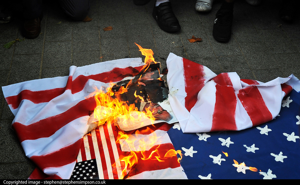 CENTRAL LONDON. British Muslim activists burn the US flag outside the American embassy in London to voice their anger at the plan by a US Christian pastor, Terry Jones,  to burn copies of the Koran on the same day. However, the US pastor has now postponed the event.  11 September 2010. STEPHEN SIMPSO