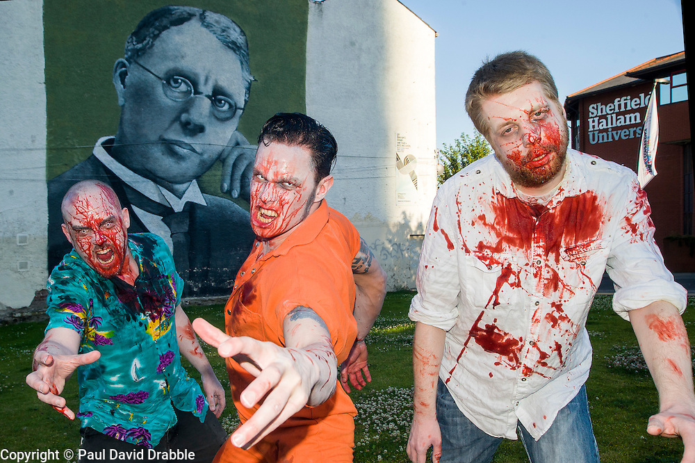 Slingshots Top Zombies Alex Noble, Noel Davies-Atack and Paul Byrne in front of the mural of Harry Brearley that commemorates 100 years since he discovered Stainless Steel in Sheffield Sheffield on Tuesday evening ahead of the game 2.8 Hours Later which reaches the city in August <br /> <br /> 30 June 2015<br />  Image &copy; Paul David Drabble <br />  www.pauldaviddrabble.co.uk