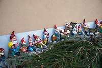 A collection of garden gnomes and farm animals positioned along a wall proves an endearing sight!