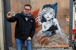 © Licensed to London News Pictures. 25/01/2016. London, UK. Members of public taking pictures of new Banksy mural criticising the use of teargas on refugees in Calais has appeared on a building opposite the French Embassy in London on Monday, 25 January 2016. Photo credit: Tolga Akmen/LNP