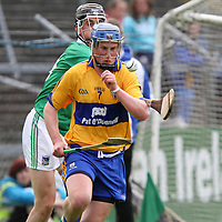 Clare's Kevin Moynihan solo's out of defence under pressure from Limerick's Dinny Ahearne in the Munster Intermediate Final at Cusack Park. - Photograph by Flann Howard