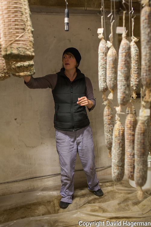 Elizabeth, a German graduate student working at Valle Unite checks salumi and pancetta in the co-op's temperature and humidity controlled meat curing room.