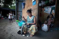 A Kachin woman mend a trousers in Woi Chyai Internal Displacement People refugee camp in Laiza village close to the China border, Myanmar on August 5, 2012. According to KIO (Kachin Independence Organization) sources around 50000 Kachin people live as refugees in those camps.