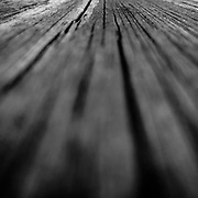 The landscape of a weathered, wooden table photographed with an iPhone 7 at minimum focus.